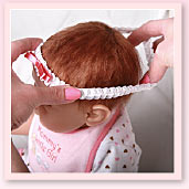 Ashton-Drake Galleries baby doll headband application tip: slip the headband on your baby doll, starting at the front of the head