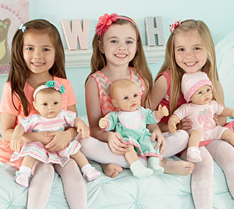 So Truly Mine doll photo gallery: three young girls sitting on a bed and holding So Truly Mine baby dolls