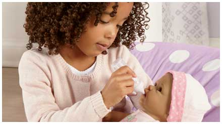 So Truly Mine doll photo gallery: a young girl feeding a So Truly Mine baby doll with a baby bottle accessory