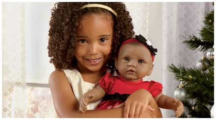 So Truly Mine doll photo gallery: a young girl holding her So Truly Mine baby doll while posing in front of a Christmas tree