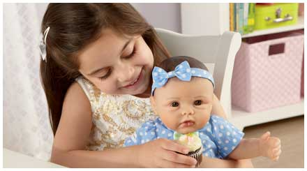 So Truly Mine doll photo gallery: a young girl feeding a So Truly Mine baby doll a cupcake