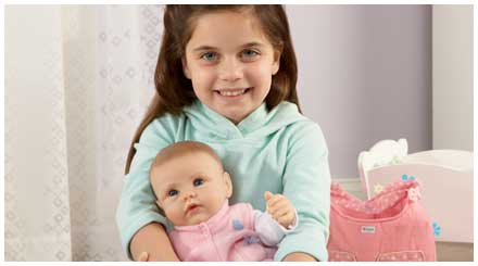 So Truly Mine doll photo gallery: a young girl holding a So Truly Mine baby doll and smiling