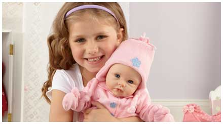 So Truly Mine doll photo gallery: a smiling young girl holding a So Truly Mine baby doll all bundled up in a pink outerwear ensemble