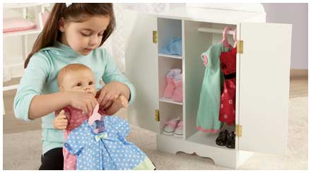 So Truly Mine doll photo gallery: a young girl changing her So Truly Mine doll's clothes from a pink ensemble to a blue ensemble